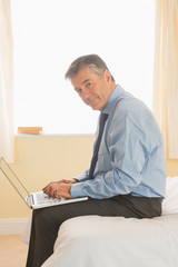Focused man using a laptop sitting on a bed