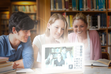 Cheerful college friends watching photos on digital interface