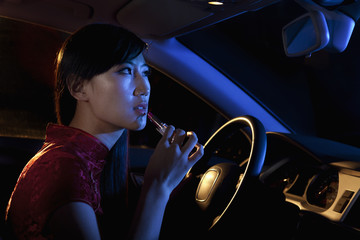 Young beautiful woman in traditional Chinese dress putting on lipstick in the rear view mirror of the car at night