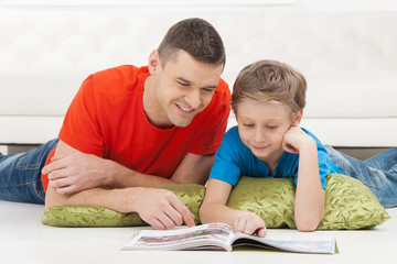 Father and son reading. Cheerful father and son reading magazine