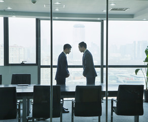 Two Businessmen Bowing to Each Other