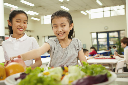 Students reaching for healthy food in school cafeteria