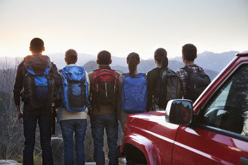 Group of people standing next to the car and looking at the mountains