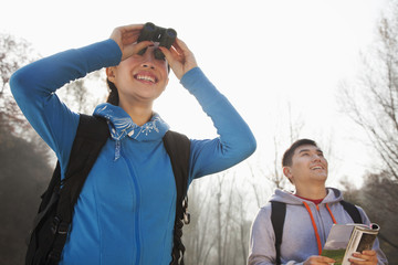 Young woman looking through binoculars, man standing in the background