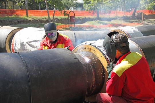 Welders welding pipes, teamwork