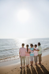 Multi generational family, arms around each other by the beach, rear view