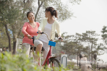 Grandmother and granddaughter riding tandem bicycle, Beijing