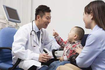 Baby Boy Playing With Doctor In Office