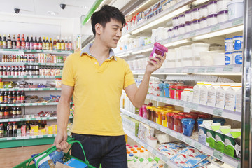 Young Man Looking At Food in Supermarket