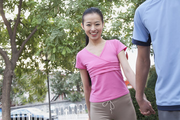 Young Woman Holding Boyfriend's Hand In Park