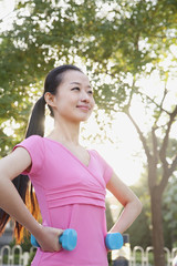 Young Woman Exercising in Park with Dumbells