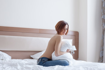 Smiling topless girl posing with pillow on bed