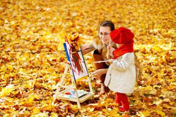 Mother and child drawing on easel in autumn park. Creative kids