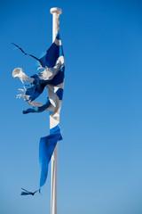 A broken greek flag with a clear blue sky