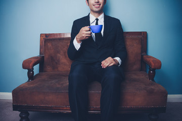 Happy young businessman drinking coffee