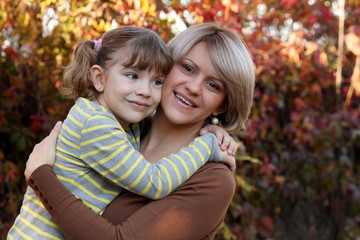 Wall Mural - happy mother and daughter portrait in autumn park