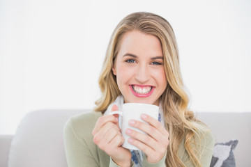 Smiling cute blonde holding cup of coffee sitting on cosy sofa