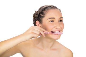 Cheerful young model brushing her teeth