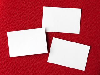 Drei Fotos Visitenkarten leer blanko auf rotem Stoff Hintergrund