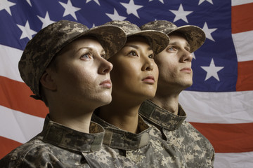 Three young military personnel in front of flag, horizontal