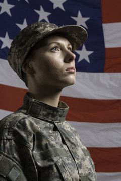 Young military woman pictured in front of US flag, vertical