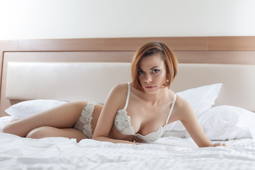 Sensual model posing in erotic lingerie on bed