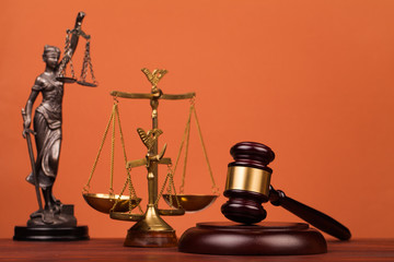 judge gavel and scales and lady of justice on table