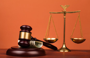 judge gavel,dollar money and scales of justice on table