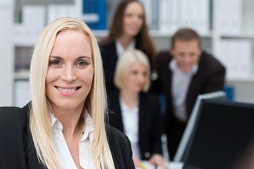 lächelnde geschäftsfrau im büro mit ihren kollegen