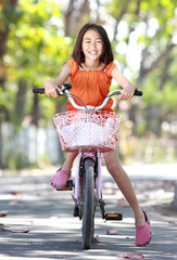 Asian cute little girl riding bicycle outdoor
