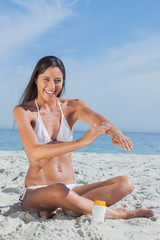 Happy woman sitting on beach applying sunscreen