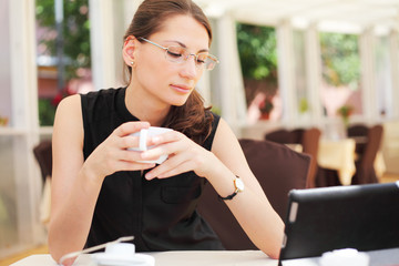 Image of young woman looking at her tablet computer and drinks c