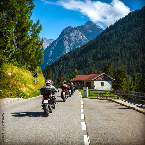 Fototapete Group of bikers on the road in Alps