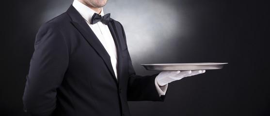 Fototapeta Waiter holding empty silver tray over black background obraz