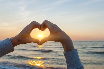 Hands in heart shape framing sun
