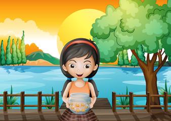 A girl at the bridge holding an aquarium