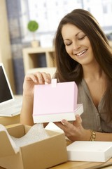 Happy woman opening postal packet