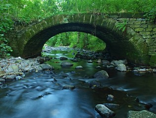 Old stony bridge of mountain stream in forest, blurred water