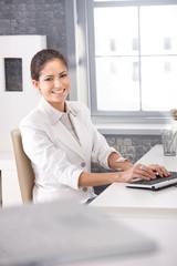 Smiling businesswoman typing on keyboard