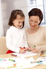 Mother and little girl drawing smiling