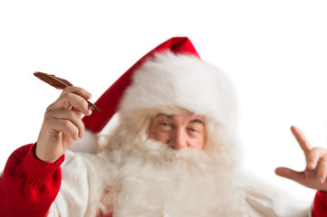 Santa Claus holding feather pen in his arm and writing