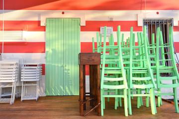 Esterno ristorante chiuso con sedie e tavoli accatastati