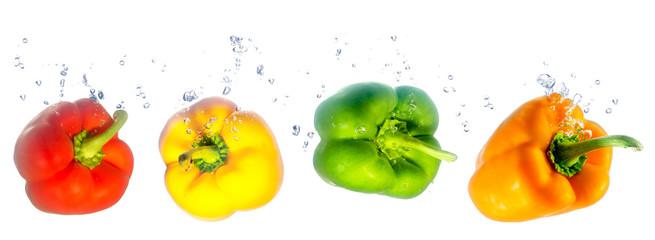 vier bunte Paprika fallen ins Wasser