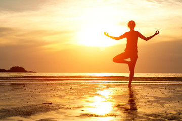 Backlit, young woman practicing yoga on the beach at sunset.