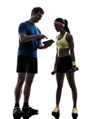 Wall Mural - woman exercising fitness  man coach using digital tablet