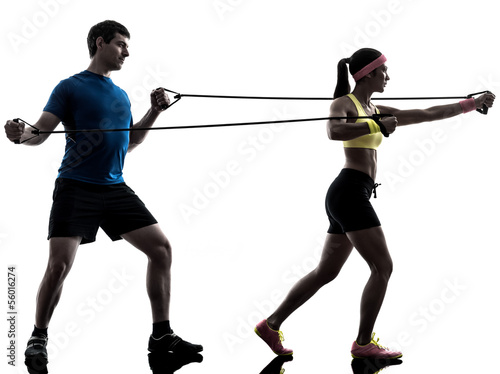 Wall mural woman exercising fitness resistance  rubber band with man coach