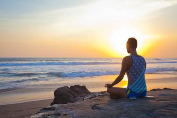 sitting man doing yoga on shore of ocean