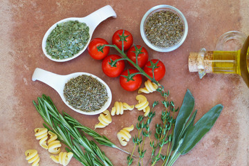Herbs, cherry tomatoes and olive oil on terracotta surface
