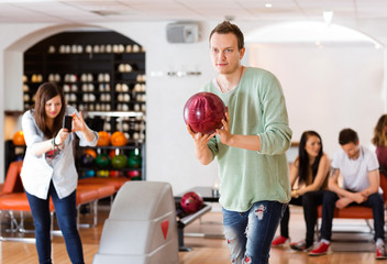 Man Bowling With Friend Photographing in Club