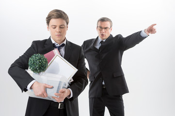 You are fired! Angry middle-aged man in formalwear shouting at y